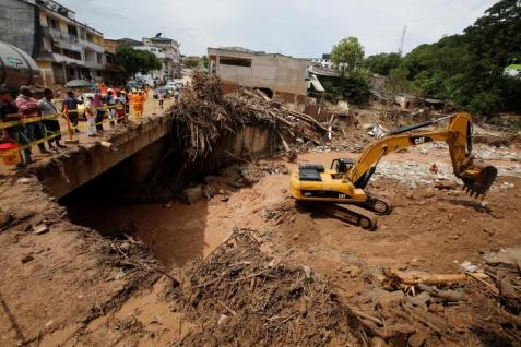 An excavator works by taking stones from the river, after flooding and mudslides caused by heavy rains, leading several rivers to overflow, pushing sediment and rocks into buildings and roads, in Mocoa, Colombia April 2, 2017. REUTERS/Jaime Saldarriaga