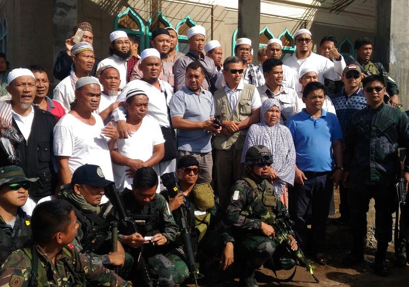 Sejumlah Warga Negara Indonesia (WNI) yang tergabung dalam jamaah tablig berfoto bersama dengan tim KBRI dan Angkatan Bersenjata Filipina sebelum dievakuasi dari Marawi City, Provinsi Lanao del Sur di Pulau Mindanao, Filipina, Kamis (1/6).
